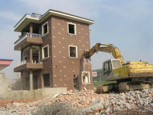在挖掘机的轰鸣声中,金方街道办事处普河村委会老爷子山林地上建盖的一排排房子轰然倒